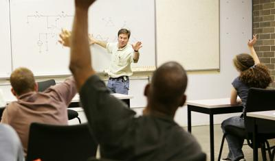 Adult education class raising hands to ask questions