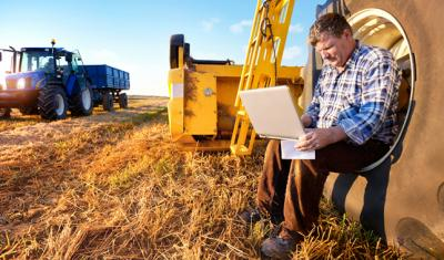 man working on laptop while sitting in tractor wheel