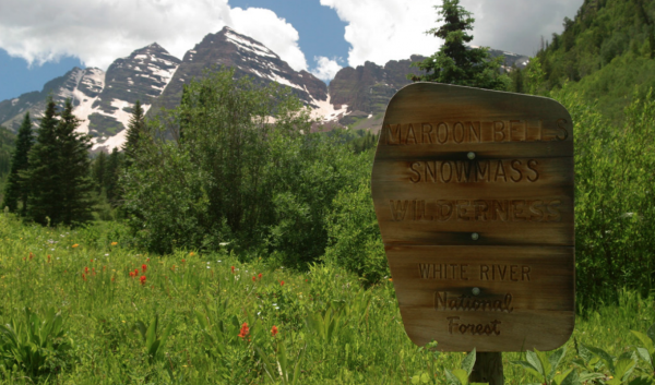 Wooden sign in front of Maroon Bells mountains